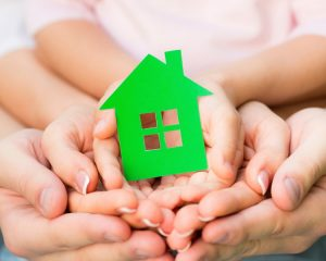 family-holding-green-paper-house-in-hands