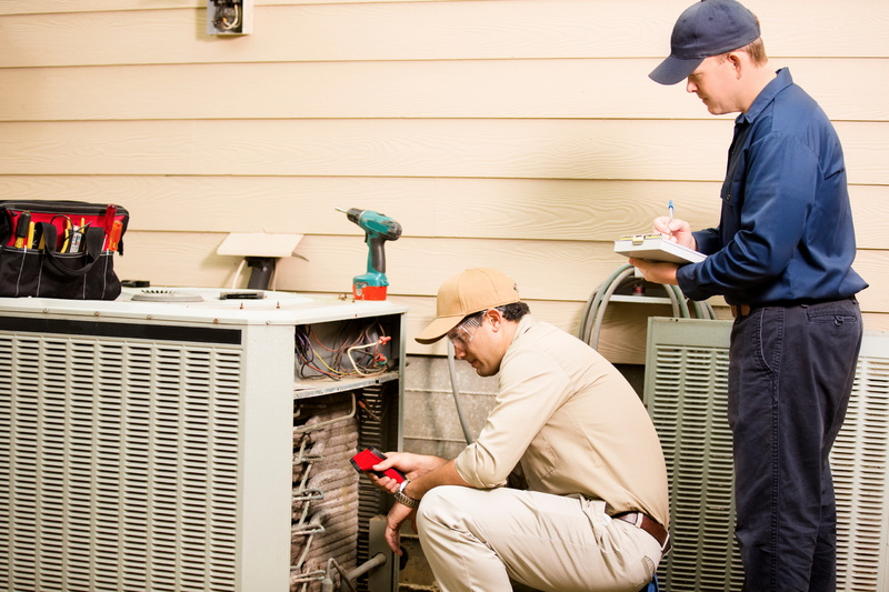 two-air-conditioning-techs-working-on-outdoor-unit